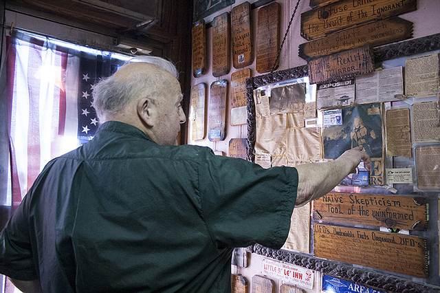 Butch mostrando su tablero lleno de recortes de diarios, dibujos y carteles.