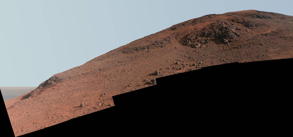 Esta escena fue tomada por Opportunity desde el valle donde se encuentra Knudsen Ridge. El color ha sido mejorado para resaltar la zona con el material rojizo, algo que también muestra un cielo celeste en el «planeta rojo»...