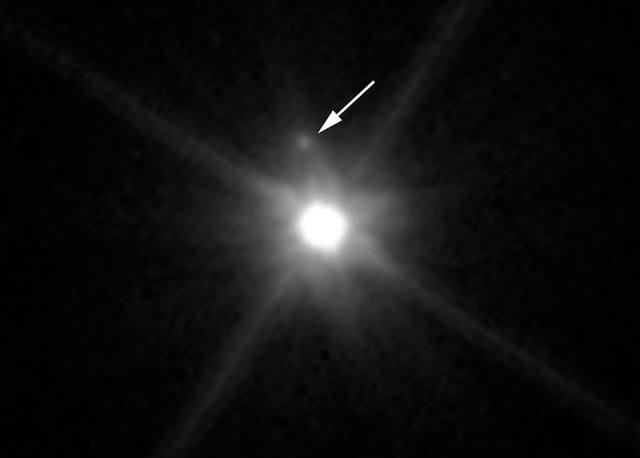 El pequeño satélite (señalado con la flecha) es apenas visible en esta imagen de Hubble debido a que se pierde en el resplandor del brillante planeta enano.