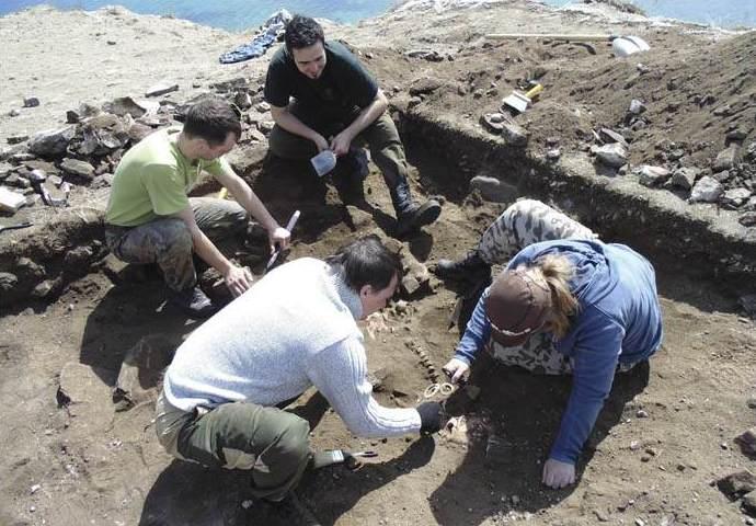 Equipo de arqueólogos excavando los restos óseos.