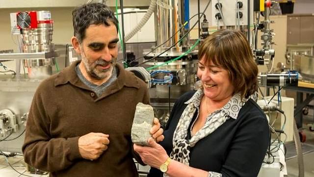 Los investigadores sostienen uno de los estromatolitos hallados en Isua, Groenlandia.
