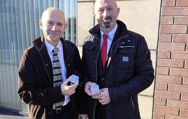 El Dr. Greer Ramsey del Museo Nacional de Irlanda del Norte (izq) junto al cazador de tesoros Brian Morton sosteniendo las dos monedas «vikingas» encontradas con un detector de metales.