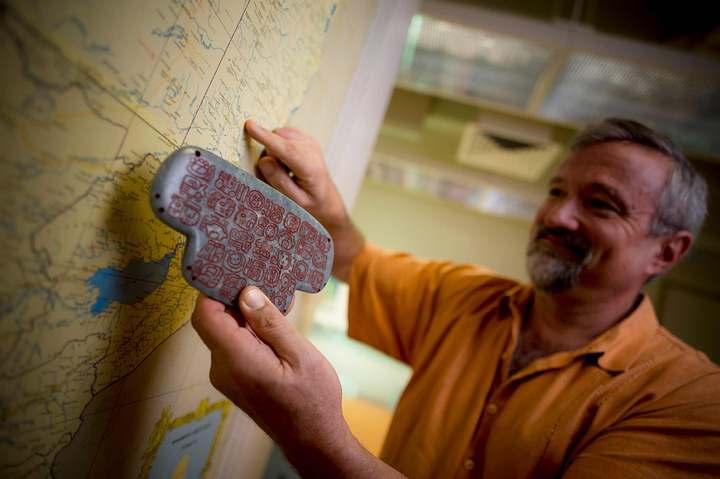 El arqueólogo Geoffrey Braswell sostiene una réplica del colgante maya de jade.