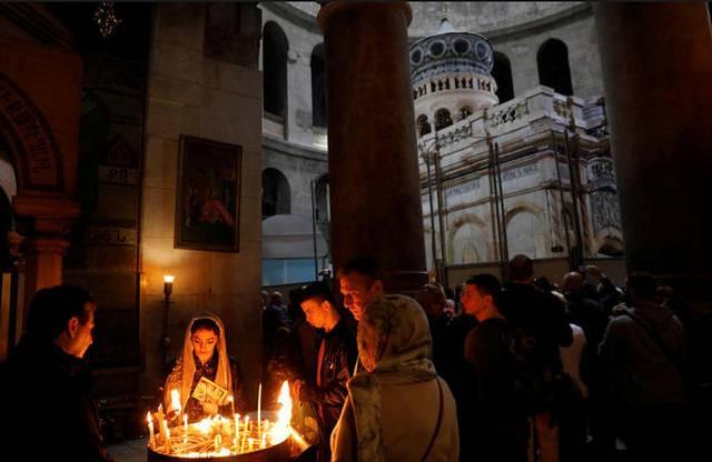 Los fieles encienden velas cerca del Edículo restaurado. Foto tomada el 20 de marzo de 2017 por Ronen Zvulun.