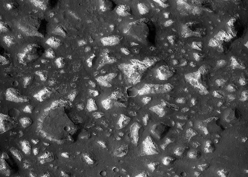 Porción de la cuenca de Eridania. Se observan bloques de depósitos minerales profundos rodeados por rocas volcánicas más jóvenes.