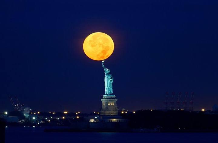 Una superluna se pone tras la Estatua de la Libertad, NY, 2015. (Crédito: Gary Hershorn/Corbis).