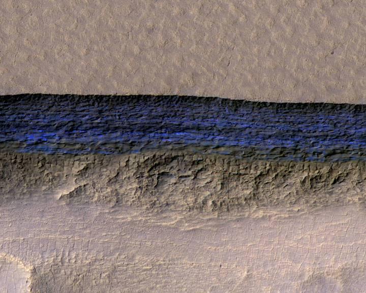Una sección transversal de hielo subterráneo está expuesta en la pendiente empinada que aparece azul brillante en esta vista desde la cámara HiRISE de la Mars Reconnaissance Orbiter de la NASA.