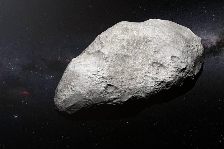 Esta ilustración muestra al asteroide exiliado 2004 EW95, el primer asteroide rico en carbono confirmado en el cinturón de Kuiper y una reliquia del Sistema Solar primordial. Probablemente, este curioso objeto se formó en el cinturón de asteroides entre Marte y Júpiter y fue lanzado a miles de millones de kilómetros, desde su lugar de origen hasta su hogar actual en el cinturón de Kuiper.