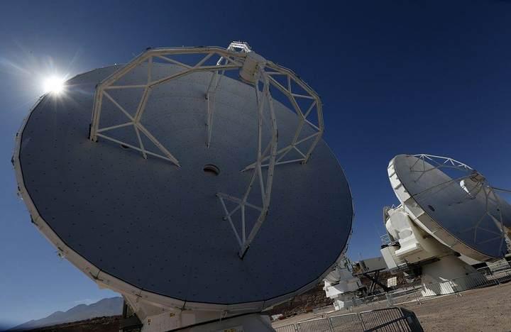 Detalle de dos antenas radiotelescópicas en movimiento del centro de apoyo de operaciones del Atacama Large Millimeter Array (ALMA).